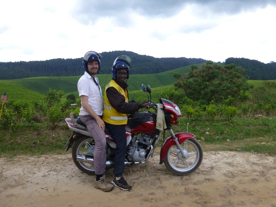 Achteraan de motoconcho, langs de theeplantages van Gisakura Tea Estate