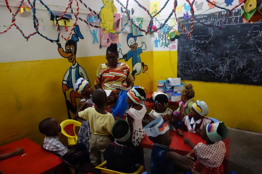 De juffrouw met een paar van haar kleuters in de kleine klas